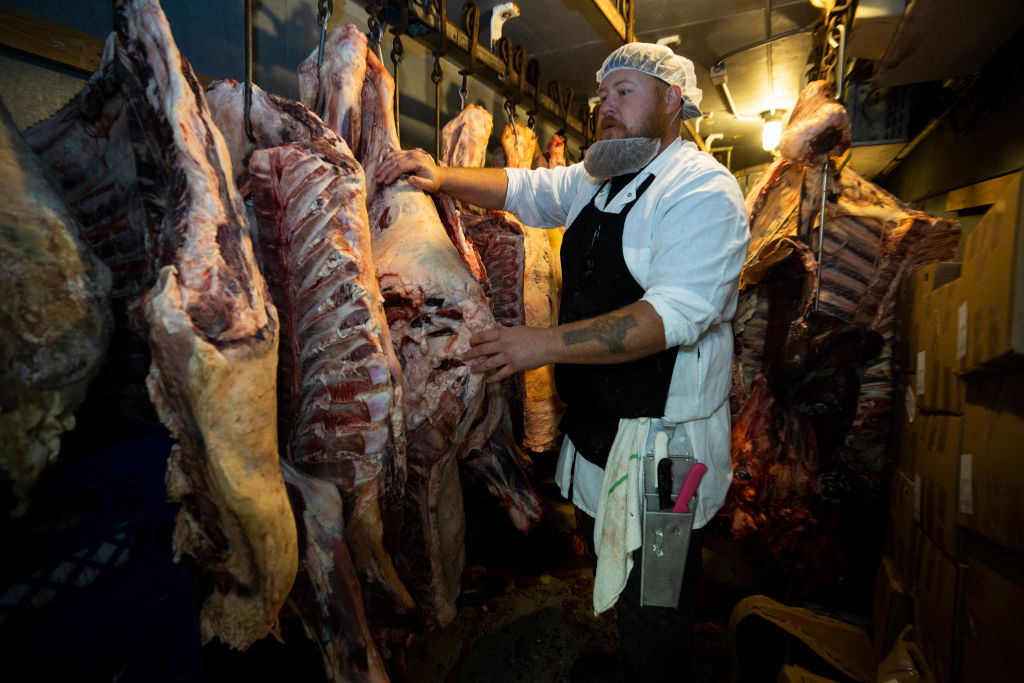 A butcher stands with sides of beef