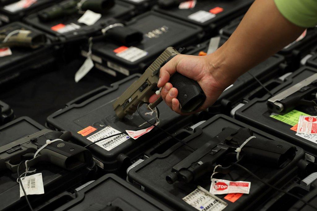 A man picks up a handgun at a gun store