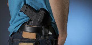 A man carries a holstered gun