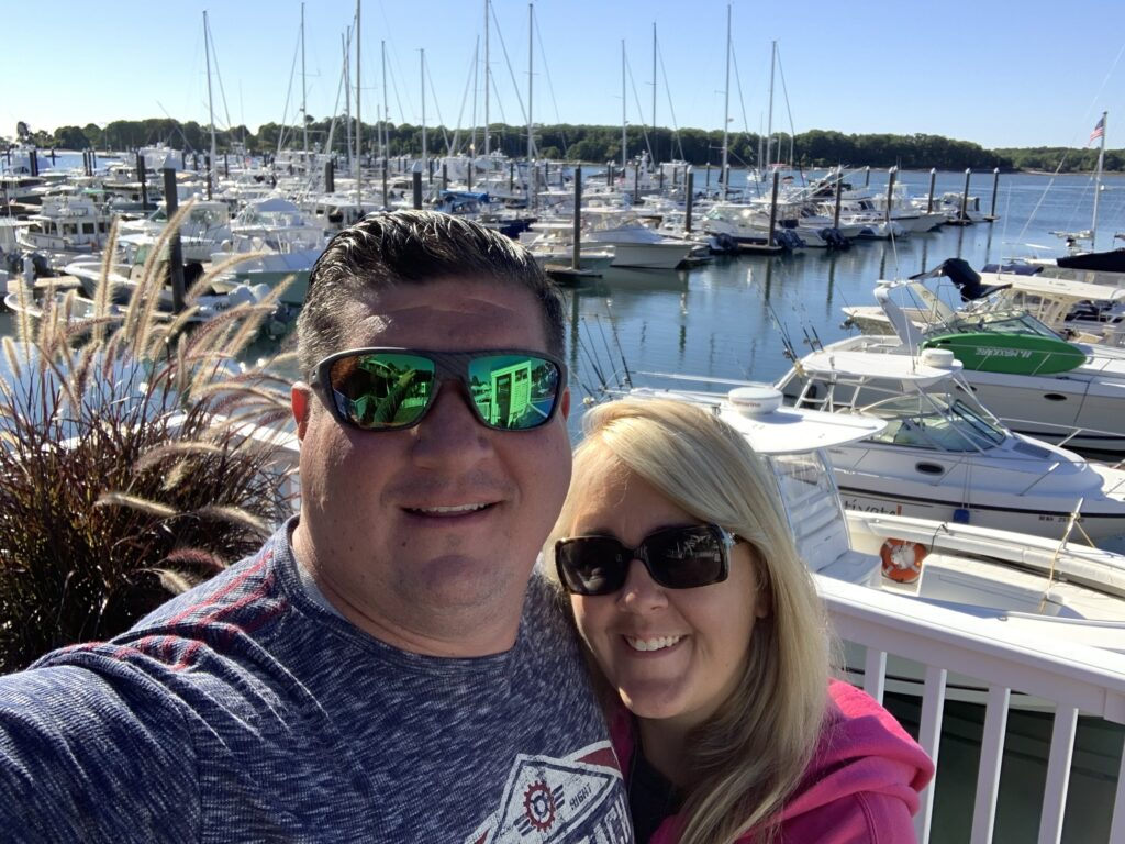 A couple poses in Portsmouth on a sunny day near the harbor.