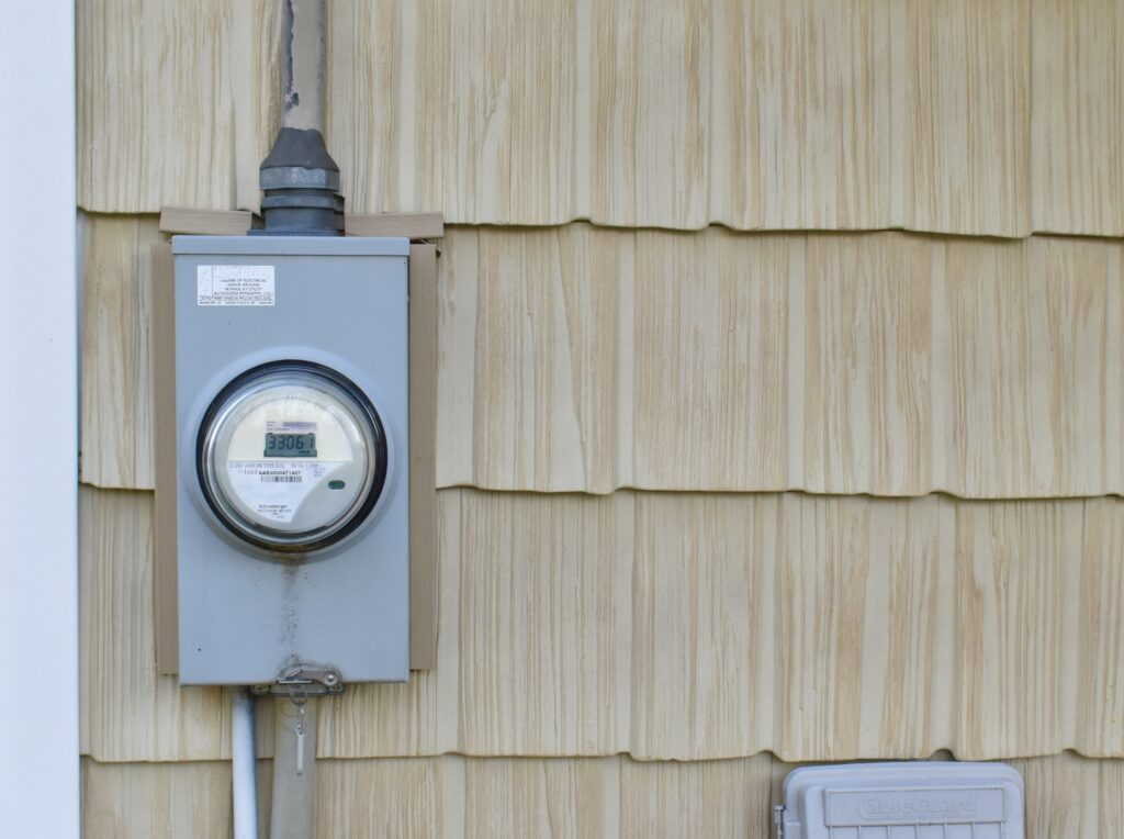 An electricity meter on the side of a house.