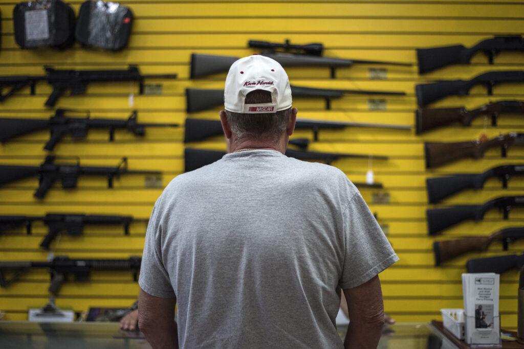A man looks at rifles at a gun shop