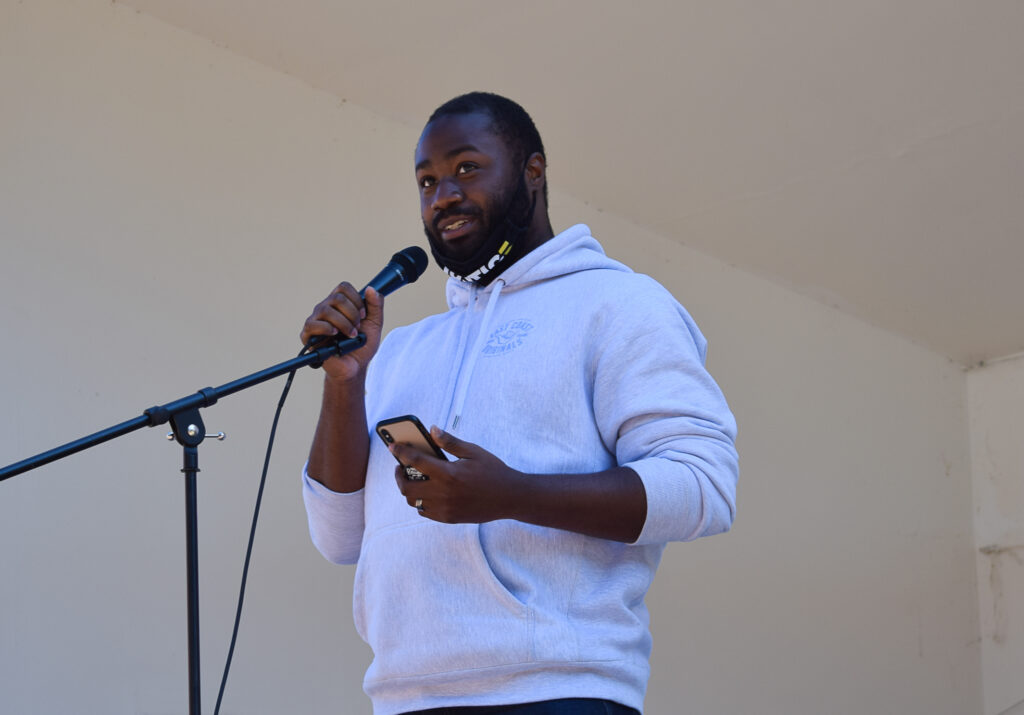 Clifton West speaks at a microphone
