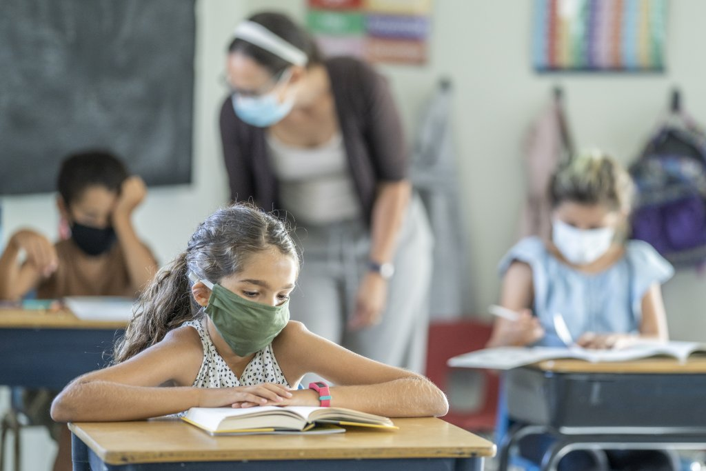 Students sit at their desks while wearing masks