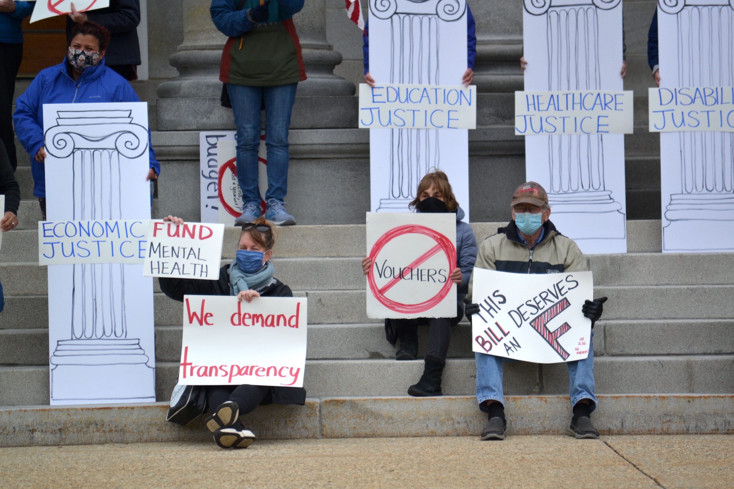 People hold signs in front of the State House