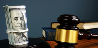 A picture of a gavel and 100 dollar bills on a fancy table