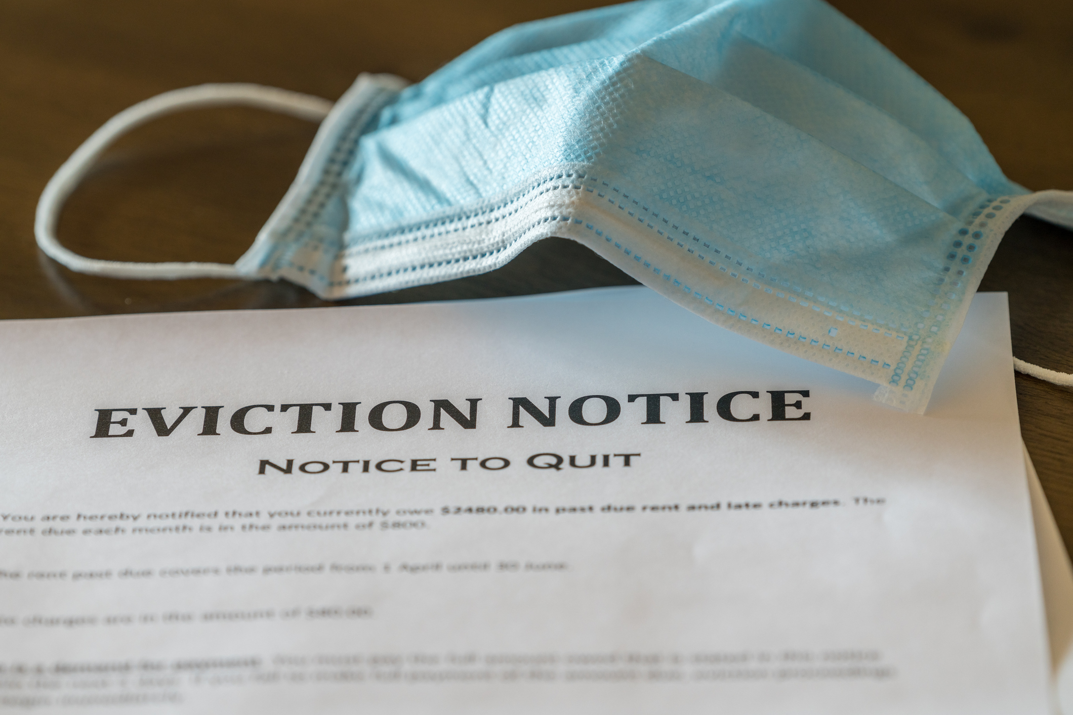 An eviction notice on a table next to a mask