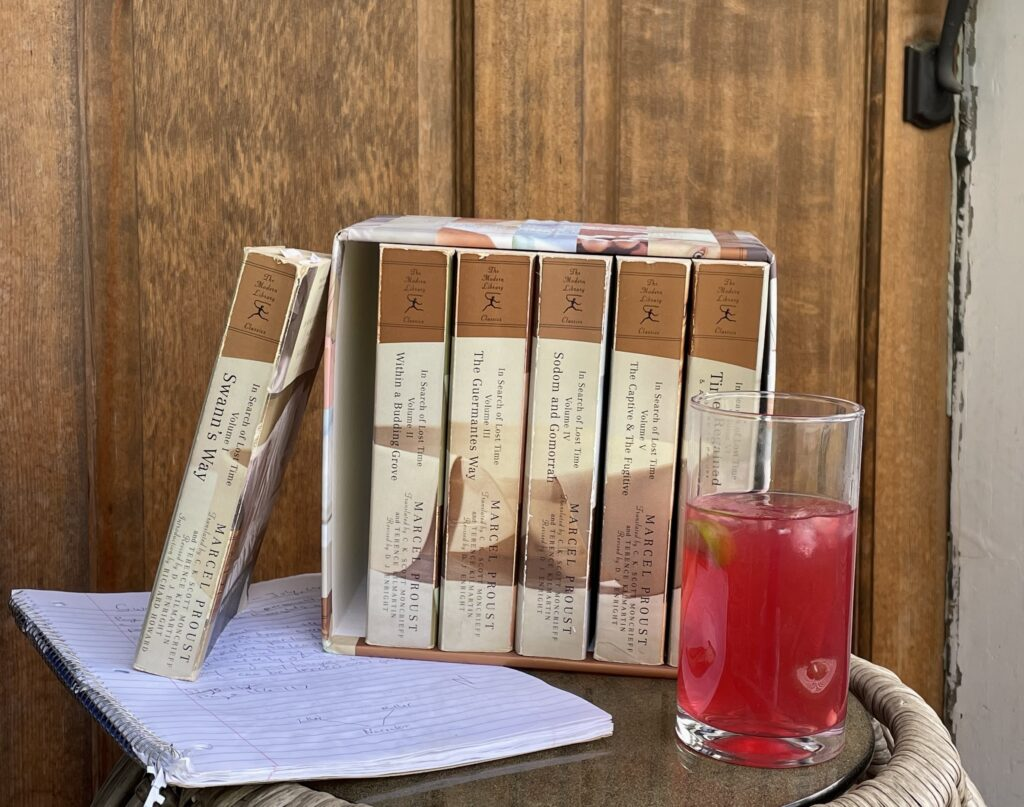 Six volumes of Marcel Proust on a table with a spiral notebook and a summery drink