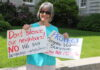 A woman holds signs opposing legislation in front of the New Hampshire state house