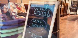 A chalkboard sign advertises job openings at the Crust and Crumb Baking Co. in Concord