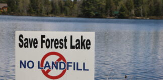A no landfill sign with the lake in the background