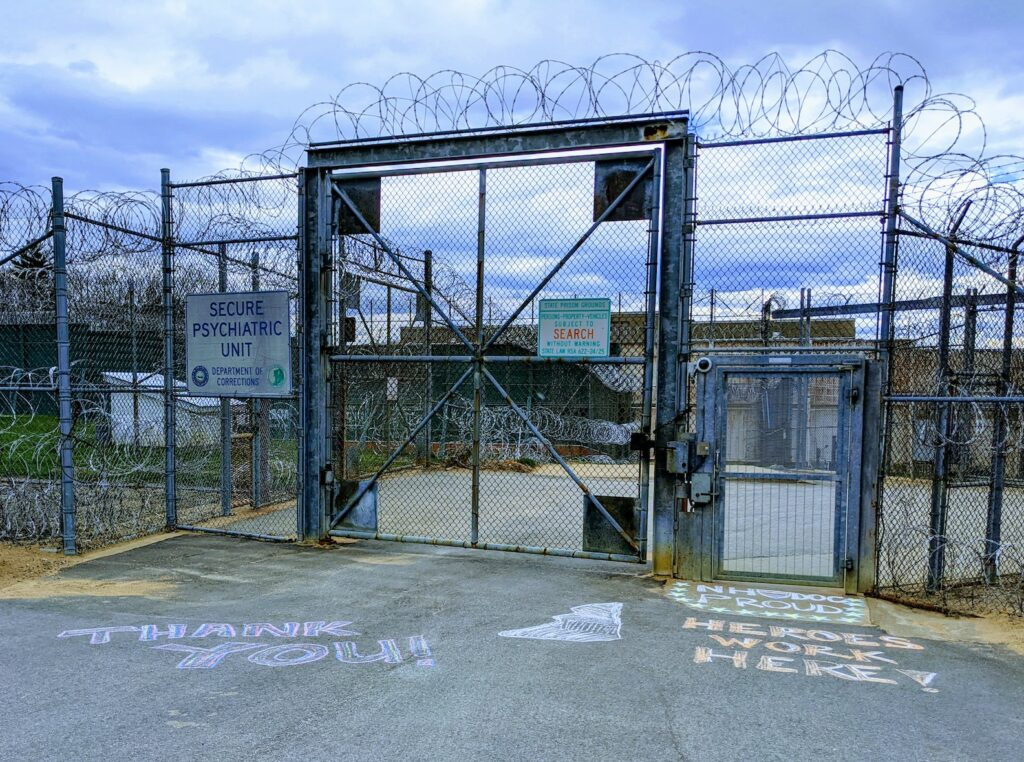 A prison fence with a sign for the Secure Psychiatric Unit