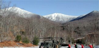 Rescuers walk in a winter field toward a helicopter with snow-capped mountain in the background