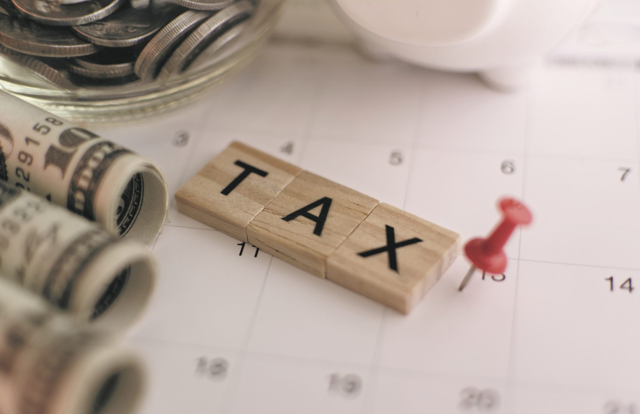 Scrabble tiles spell the word tax next to rolls of money and a red pushpin marking tax day on a calendar