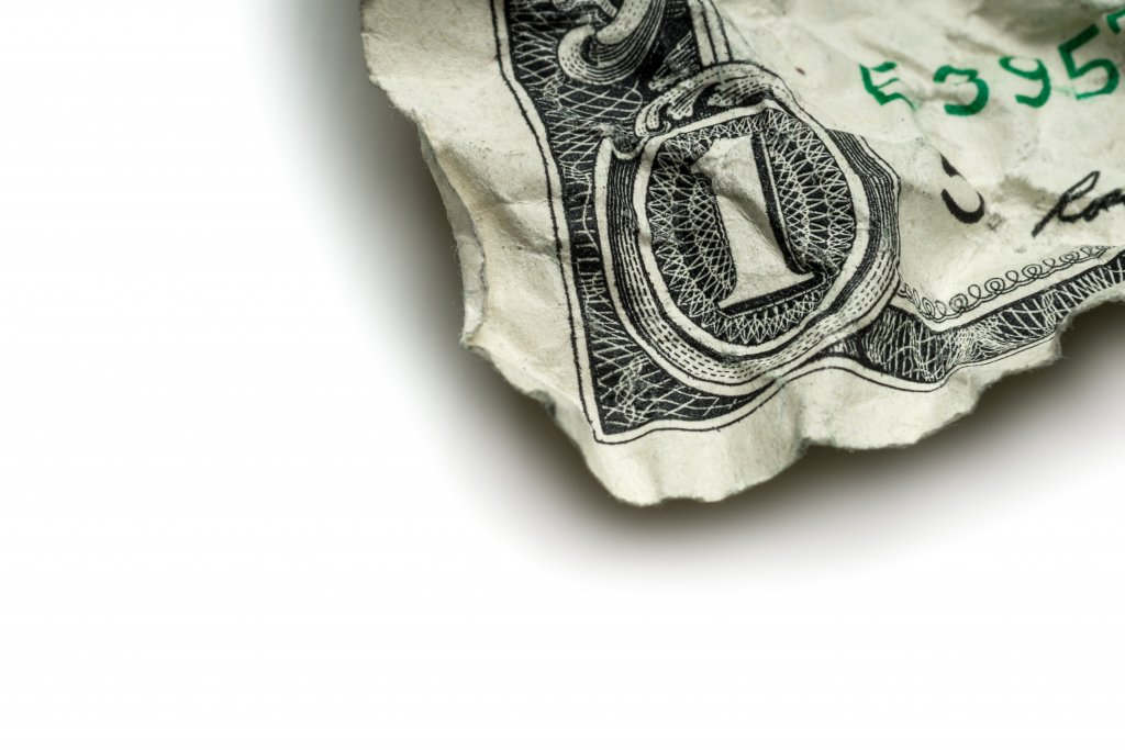The corner of a crumpled up dollar bill
