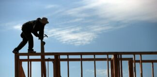 A builder works on the frame of a house