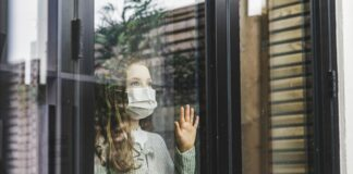Girl with a mask looking out a window