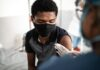 A person wearing a mask gets vaccinated