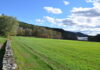 Blow-Me-Down Farm in Cornish. A green field stretches toward mountains on the horizon