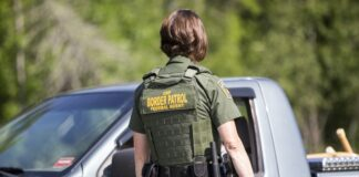 A border patrol agent talks to someone in a gray pickup truck