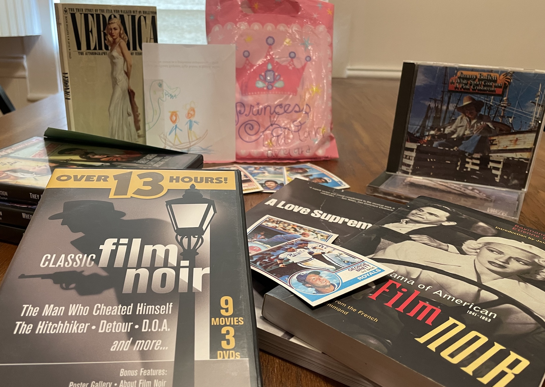 On a table are film noir DVDs, Jimmy Buffett CDs, baseball cards, books and a pink plastic Princess bag
