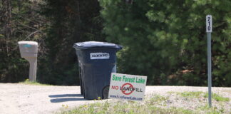 A Casella trash bin next to a sign opposing the landfill