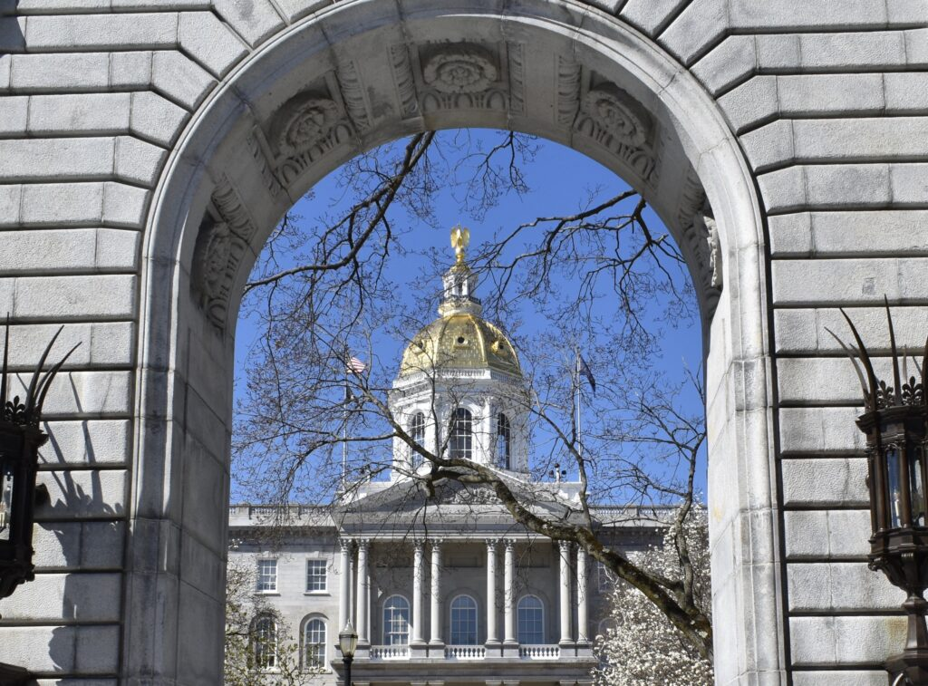 The state house as viewed through a stone arch