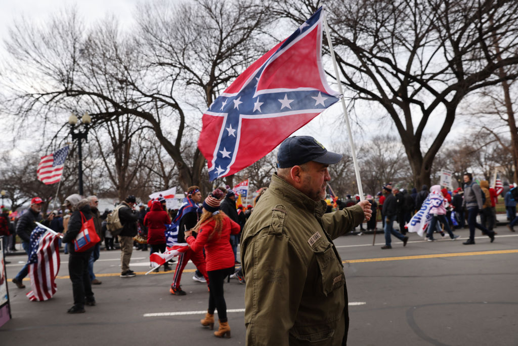 A man carries a Confederate flag while marching in Washington on Jan. 6.