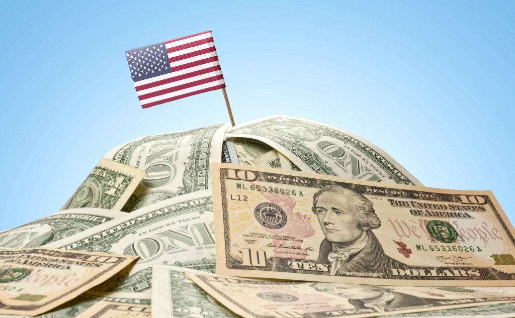 An American flag sticking out of a pile of paper money