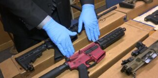 Guns on a table as gloved hands reach out