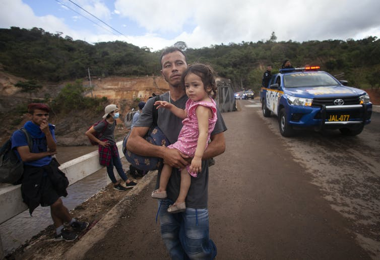 A man holds a young girl while walking along a highway in Guatemala.