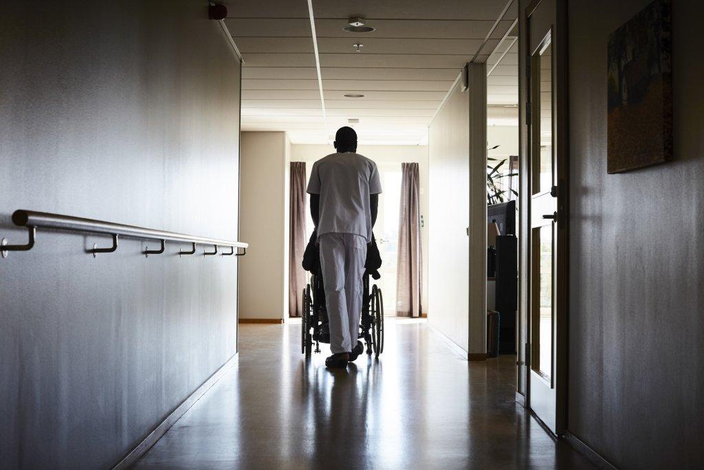 A nurse pushes a patient down an empty hallway.