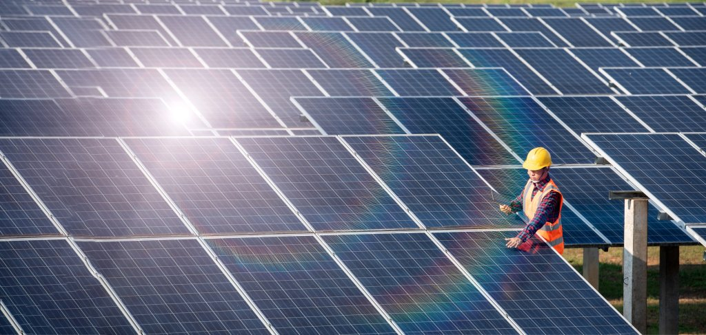 A worker checks on solar panels