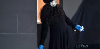 A masked woman unlocks a store at the a Mall