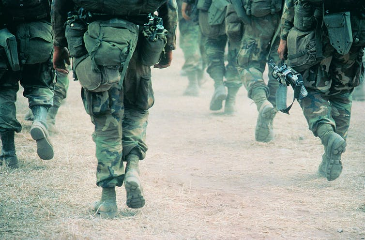 Several soldiers march away from the camera