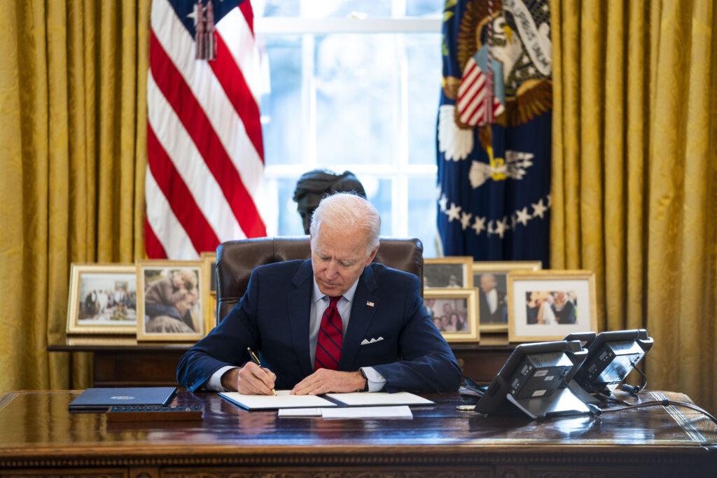 Joe Biden signs papers at his desk in the Oval Office