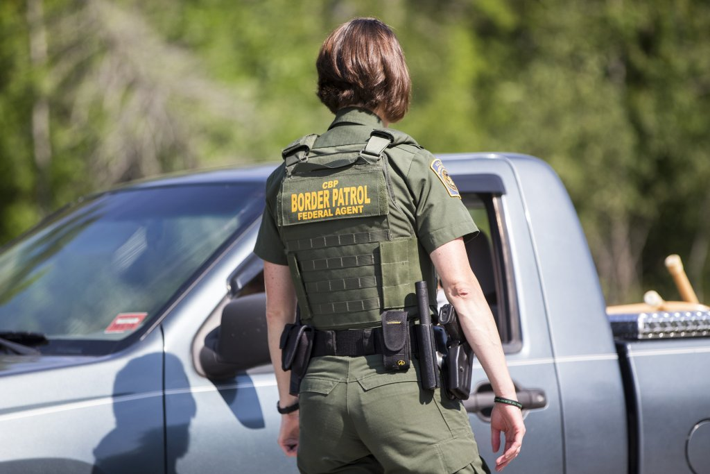 A border patrol agent talks to a driver sitting in a gray pickup truck