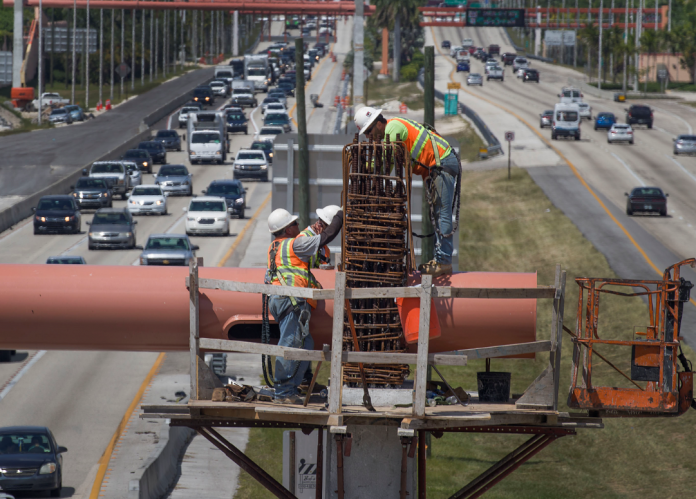 Workers on a bridge over a turnpike