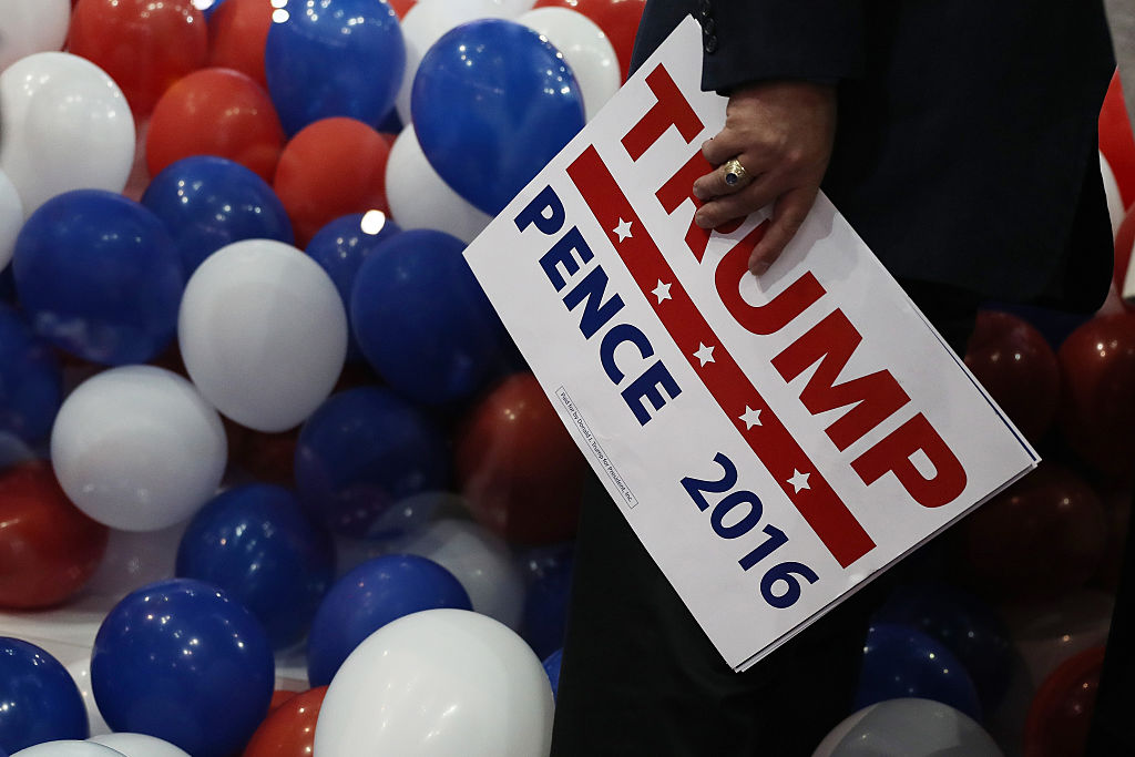 A person holds a Trump-Pence 2016 sign near red, white, and blue balloons
