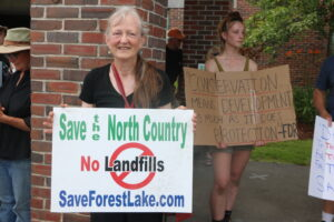 A woman holds a sign in opposition to the landfill