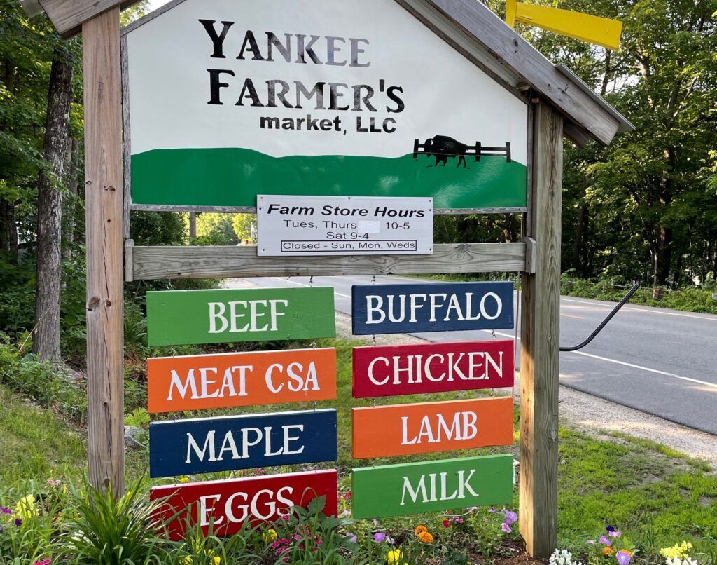 A green and white sign for the Yankee Farmer's Market in Warner, with colorful signs for individual products like eggs, lamb, and buffalo