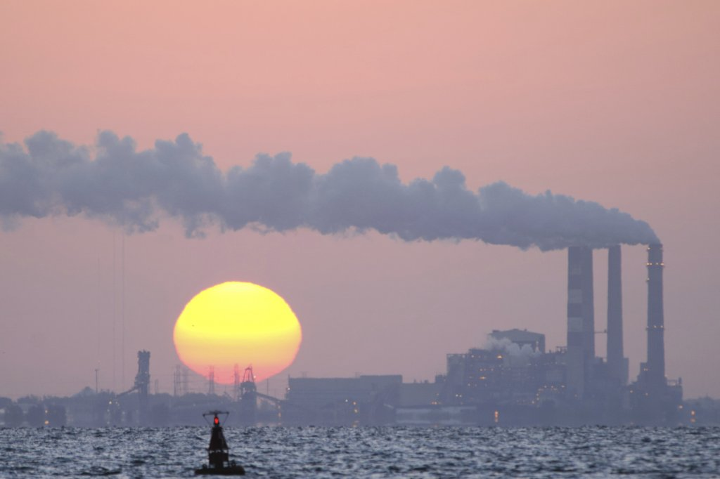 A smoke stack is visible next to a setting sun