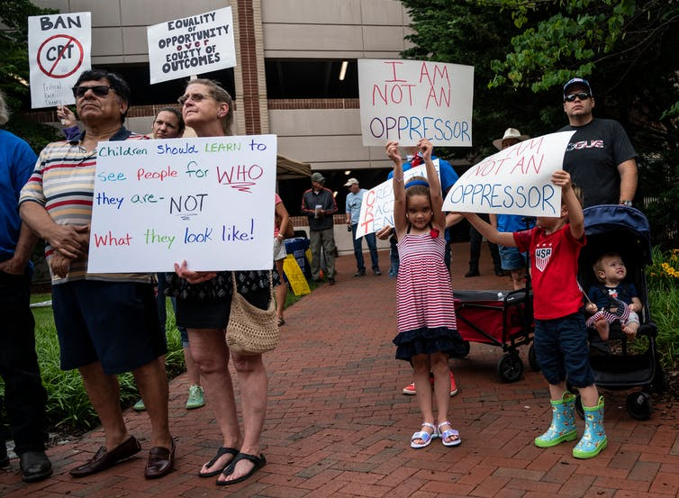 """People rally against """"critical race theory"""" by holding up signs"""