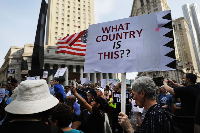 """Protesters at a rally in New York hold up a sign that says """"What country is this?"""""""