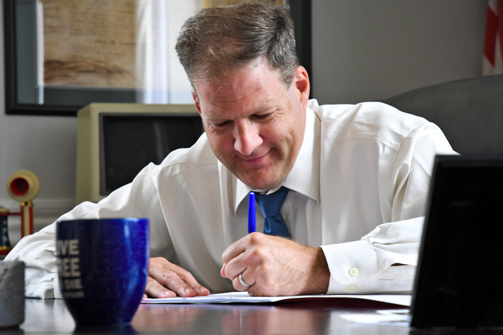 Gov. Chris Sununu, wearing a white shirt and tie, sits at a desk to sign a document.