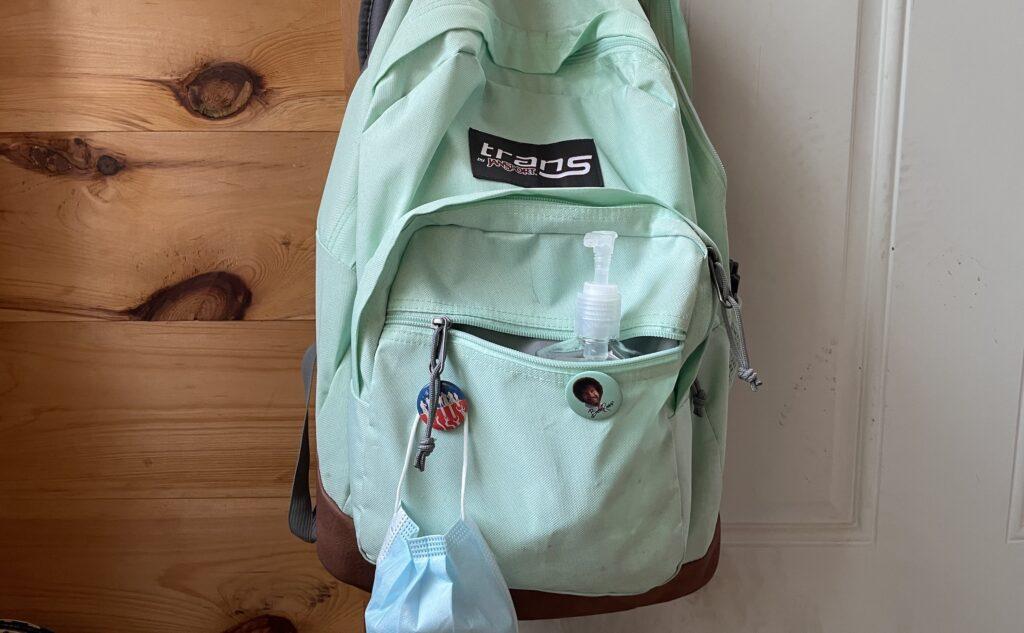 An seafoam green backpack hanging on a doorknob