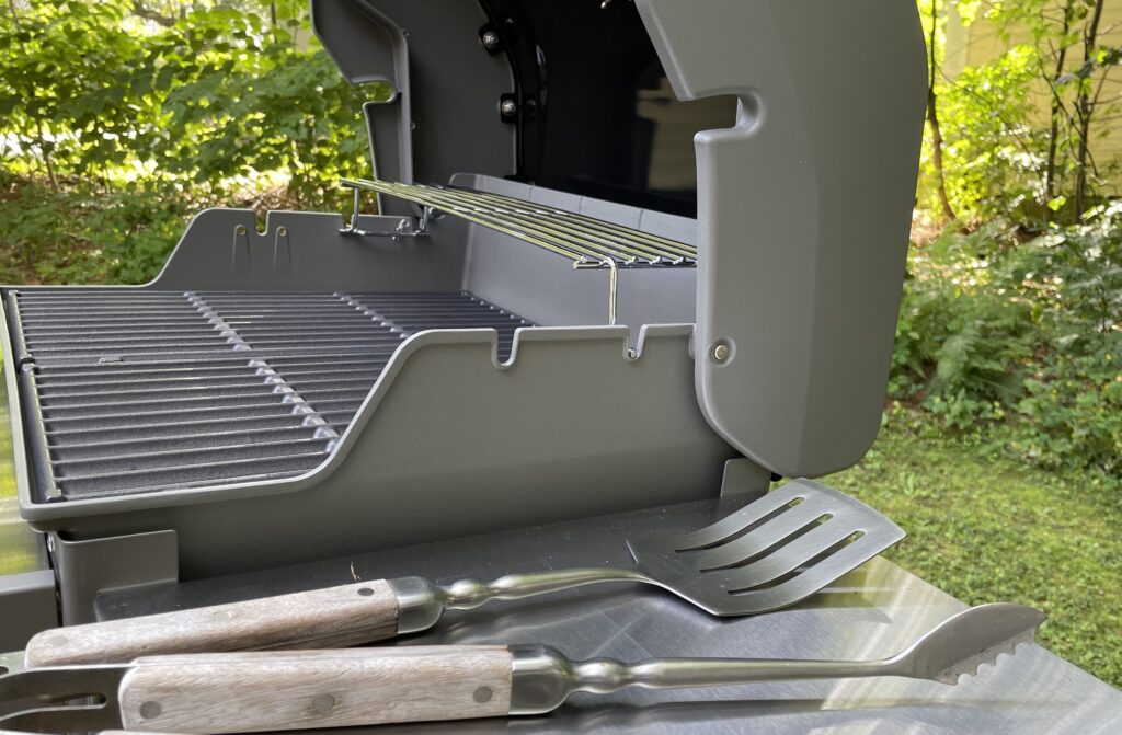 An open gas grill with a spatula and tongs in the foreground