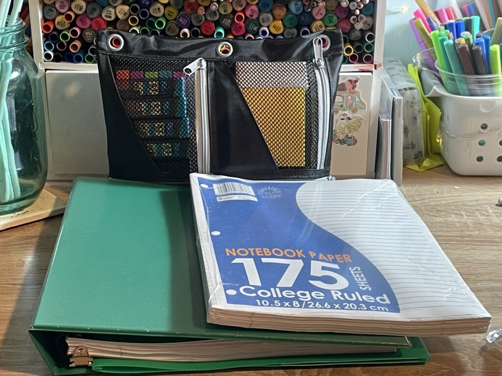 A desk with a binder and notebook paper, with a pencil case and markers in the background.