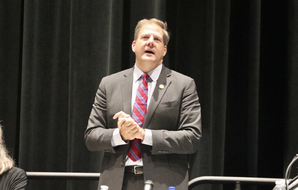 Gov. Chris Sununu stands during a meeting