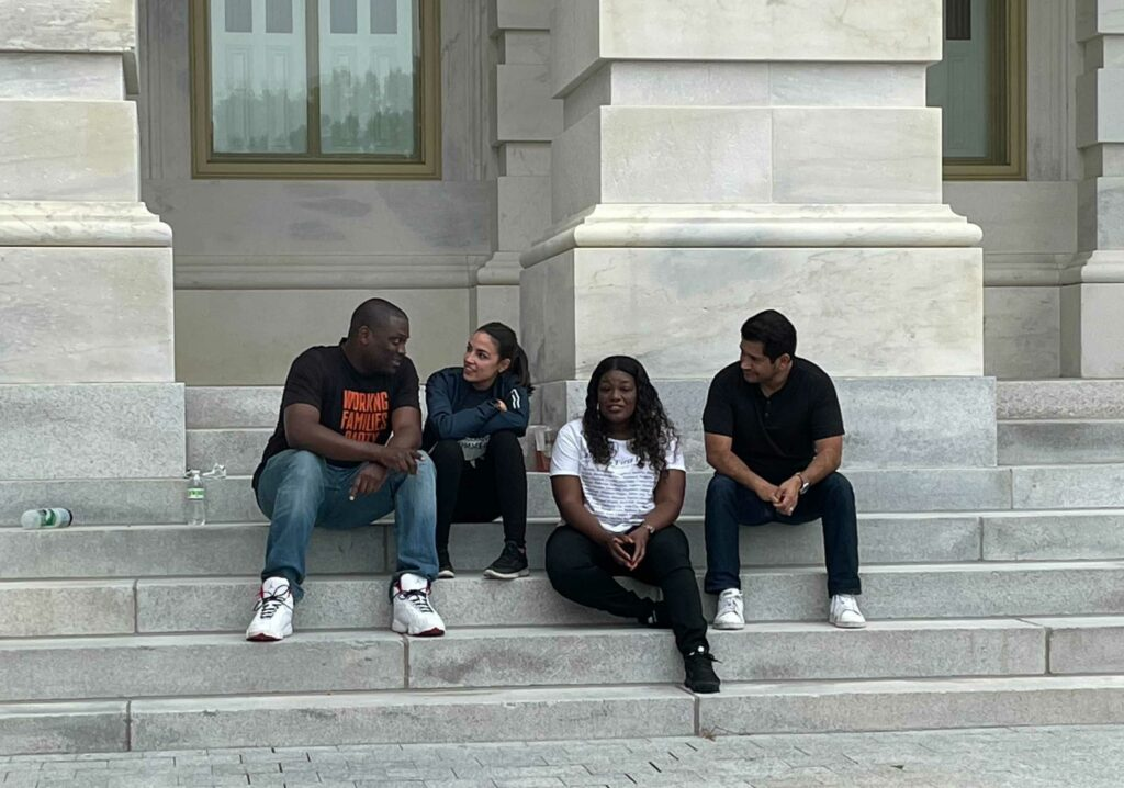 From left, U.S. Reps. Mondaire Jones and Alexandria Ocasio-Cortez of New York, Cori Bush of Missouri, and Jimmy Gomez of California sit on the steps of the Capitol